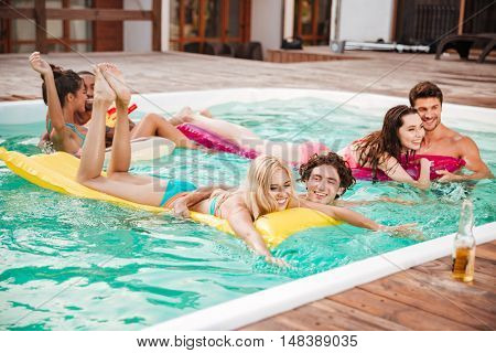 Happy young couples swimming in pool and having fun