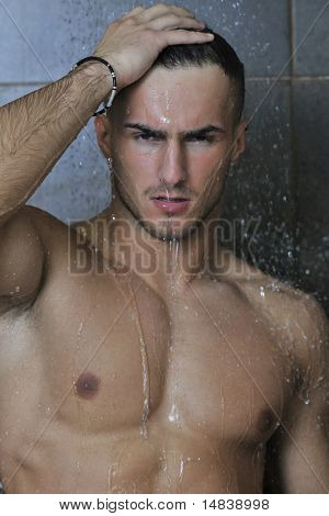 young good looking and attractive man with muscular body wet taking showe in bath with black tiles in background