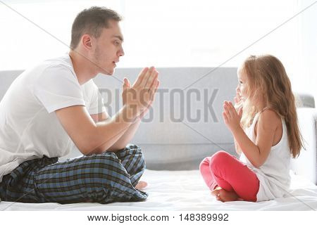 Happy father playing with daughter in bed