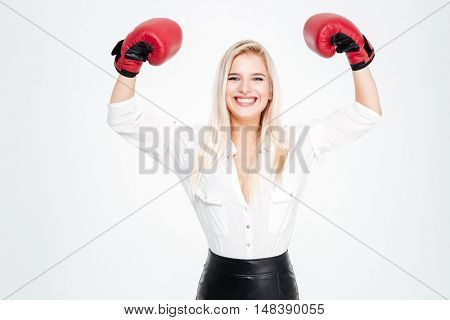 Cheerful young businesswoman in boxing gloves with raised hands over white background