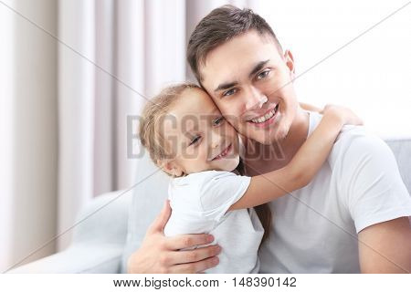 Happy father with daughter on couch
