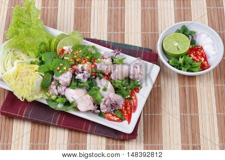 Spicy and sour mixed herb salad with squid wrap minced pork. Side view.