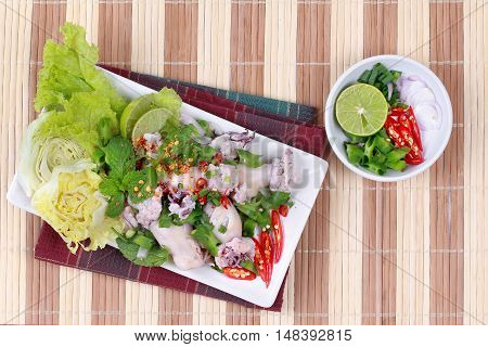 Spicy and sour mixed herb salad with squid wrap minced pork. Top view.
