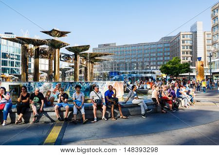 Berlin Germany August 27 2016: People are resting nearby the fountain on Alexanderplatz summer time