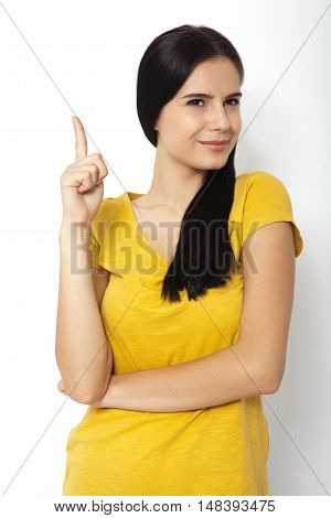 Girl pointing at. Young beautiful sexy woman showing on empty space. Portrait of smiling Asian, white Caucasian isolated on white background.