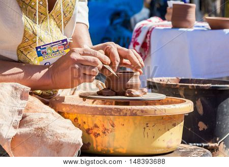 Zaporizhia/Ukraine- September  17, 2016: Family festival of homemade pickled canned vegetables and preserves. Outdoors pottery workshop.  Closeup hands of potter, presenting  process of ceramic jug creating on a turning wheel.