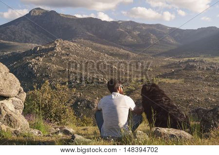 Young man and his dog enjoying sitting the sunset together at the top of the mountain