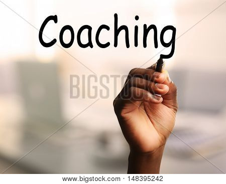Human hand writing word COACHING at transparent whiteboard on blurred background
