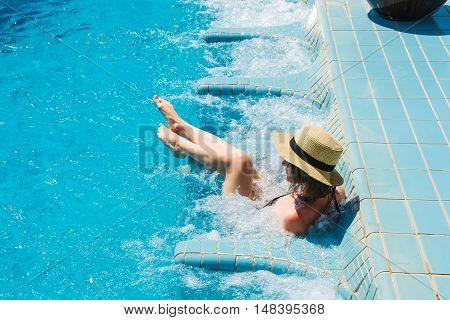 Photo of the Girl in hat relaxing in spa swimming pool and jacuzzi, enjoying vacation. Luxuty lifestyle, healthy feet, skin care concept.
