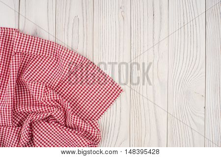 Red folded tablecloth over bleached wooden table. Top view.