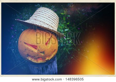 Scary Pumpkin in a straw hat on halloween on background of grass in a meadow