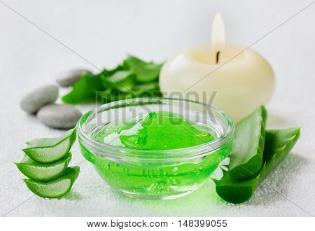 Fresh aloe vera leaf and aloe gel with burning candles on white surface. Cosmetic, medicinal and beauty concept.