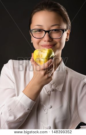 beautiful smiling girl eating green apple isolated on black background