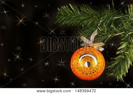 Big orange shiny mirror ball on new year tree on a black background with colorful stars.