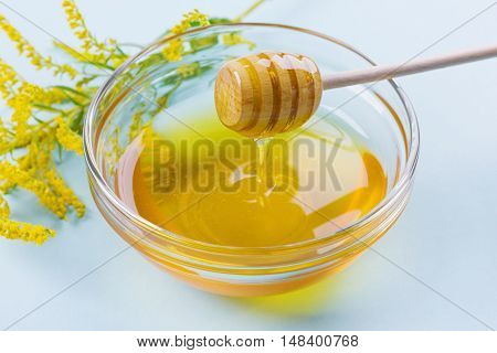 Honey drip from a wooden dipper in glass bowl on a blue background, selective focus.