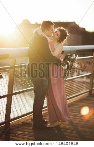 Stylish loving wedding couple, groom, bride with pink dress kissing and hugging on a bridge at sunset.