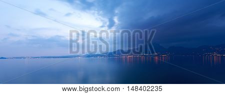 Lago di Garda at night (Garda Lake) the largest Italian lake of glacial origin with the lights of the coast of Lombardy Italy