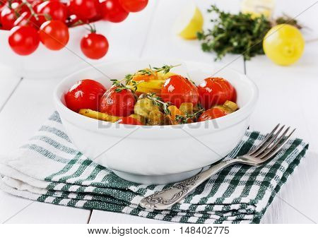 Young baked potatoes with carrots, mushrooms and grilled cherry tomatoes in white plate.