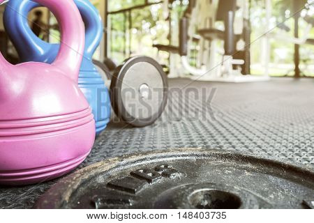 exercise weights - kettlebell and dumbbells on floor in fitness gym - a home gym concept