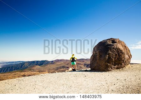 Woman successful hiking climbing in mountains motivation and inspiration beautiful view. Female hiker with backpack looking from mountain top. Inspirational landscape on Teide Tenerife in Spain.
