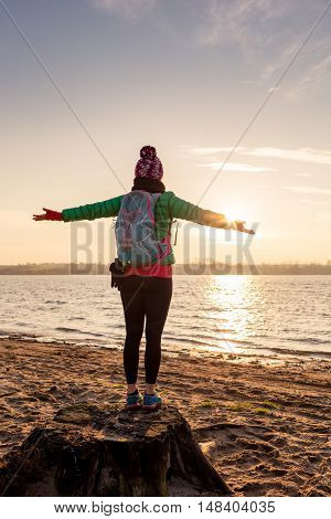 Woman hiker with arms outstretched enyoing sunrise and lake relaxing on beach and sand. Happy female celebrating beautiful morning with backpack looking at inspirational landscape on beach.
