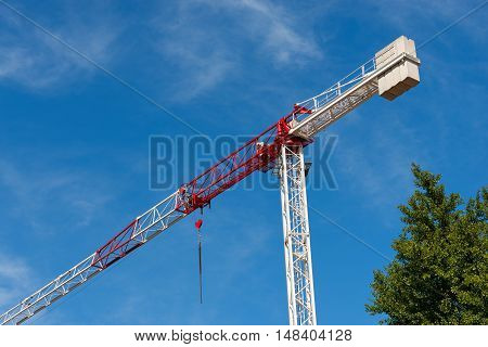 Detail of a red and white crane on blue sky with clouds and a green tree. Construction site