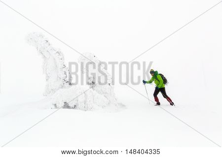 Winter hike climbing in white winter snowy mountains. Man hiking trekking in winter. Travel recreation fitness and healthy lifestyle in beautiful snowy nature. Inspirational white winter landscape.