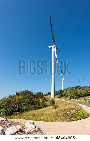 Two white and red wind turbines on a green hill with clear blue sky and power lines. Verona Italy