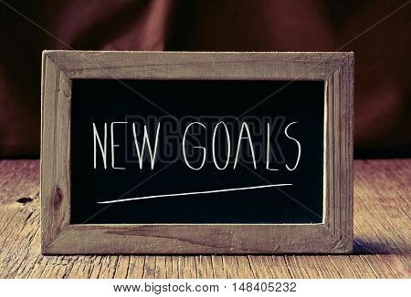 a wooden-framed chalkboard with the text new goals written in it, placed on a rustic wooden surface
