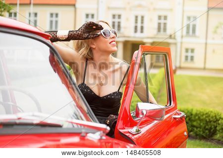 Fancy woman standing next to the car and enjoying