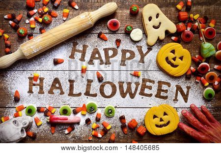 high-angle shot of a wooden table sprinkled with icing sugar where you can read the text Happy Halloween, some different candies and cookies, some scary ornaments and a rolling pin