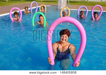 Group portrait of senior citizens about to do aqua gym with soft foam noodles in outdoor swimming pool.