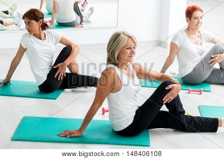 Group of middle aged women warming up in gym.Threesome sitting on floor on rubber mattresses.