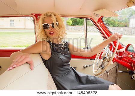 Fancy woman driving a red retro car