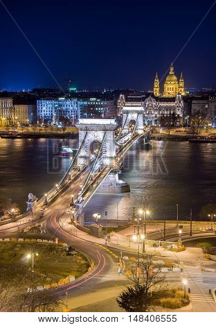 Night view of the Szechenyi Chain Bridge over Danube River and church St. Stephen's Basilica in Budapest, Hungary. View from Royal Palace in Buda Castle.