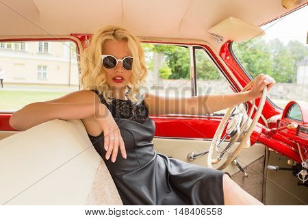 Glamorous and sexy  woman driving a vintage car