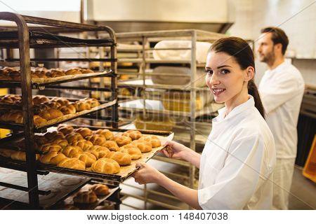 Female baker holding a tray of michetta in bakery shop
