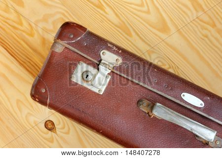Leather worn retro suitcase standing on a light wooden background / luggage for a cruise round the world