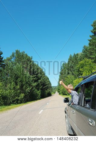 Boy waving from the moving car. travel concept.