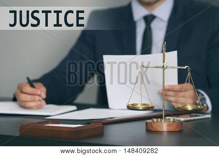 JUSTICE. Scales of justice on table, closeup