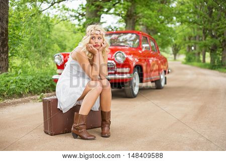 Sad woman sitting on suitcase and waiting for help