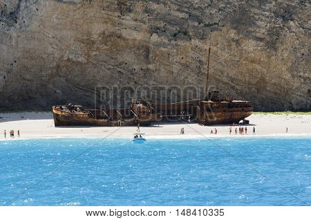 Zakynthos Greece July 15 2016: Shipwreck beach on the island of Zakynthos seen from the sea on the shore some tourists a taxi boat leaves the shore