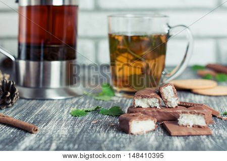Latte with mint syrup. Hot mint tea with chocolate candy and cookies on old table