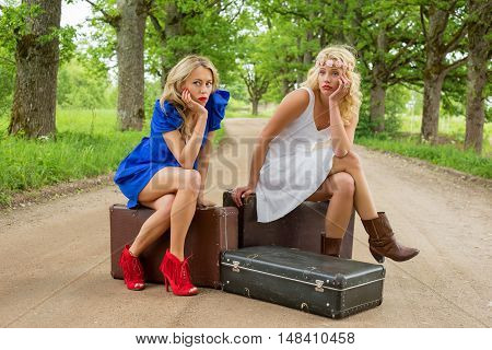 Two women on dirt road sitting on the suitcases and waiting for help