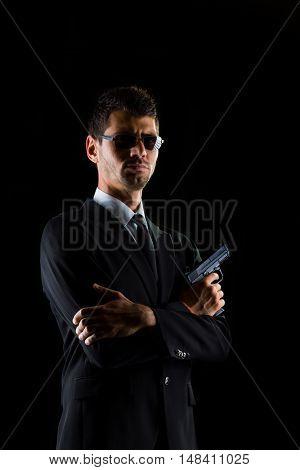 man holding a gun on dark background