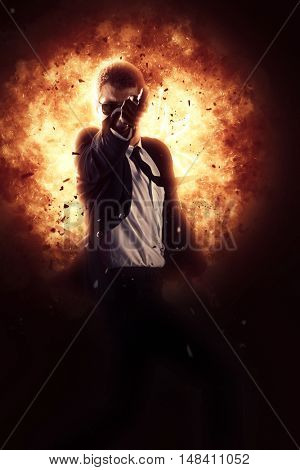 Brave cool man holding a gun on explosion background
