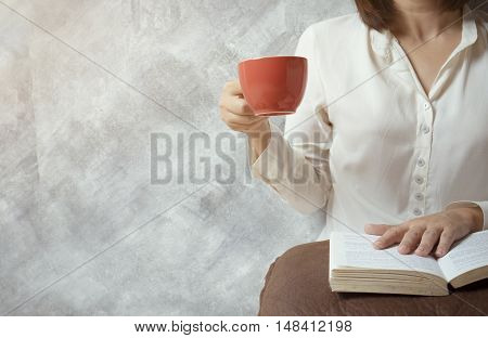 A Girl reading a book on pillow and drinking coffee. Relax and education concept.