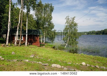 House on the lake traces of grass and trees. Karelia.