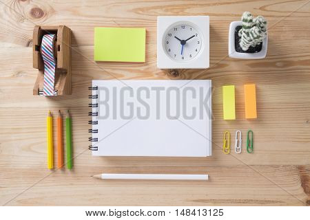 Topview of office stuff on wooden working table. Mock up. Sticky tape note paper white blank notebook post-it note pencil clock paper clip colour pencil and cattus.