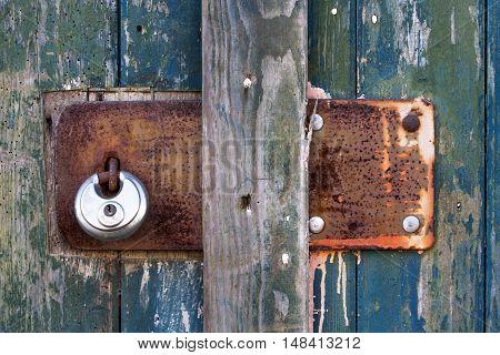 Vintage rusty metal plate with padlock on old wooden weathered door
